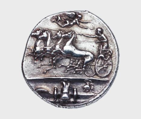 Αργυρό δεκάδραχμον Συρακουσών, αρχές 4ου αι. π.Χ. Νομισματικό Μουσείο, Αθήνα. Η Νίκη υπερίπταται των αλόγων και στεφανώνει τον ηνίοχο του τεθρίππου. Στο έξεργο απεικονίζεται αμυντικός οπλισμός δηλ. ασπίδα, θώρακας, περικνημίδες και περικεφαλαία. Τα όπλα περιγράφονται ως «ΑΘΛΑ» ένας όρος που θα μπορούσε να ερμηνευθεί ως βραβεία κάποιου αγώνα ή πολεμικά τρόπαια.