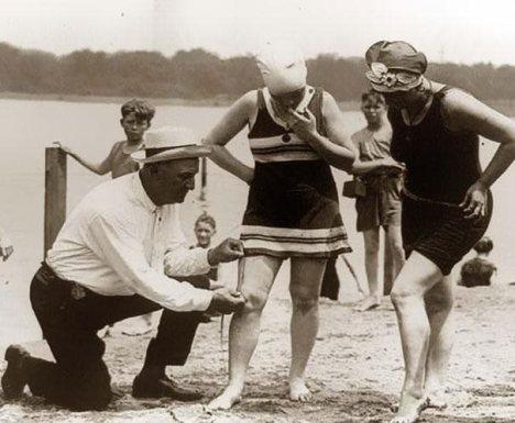 Ένας κρατικός υπάλληλος κρατώντας ένα μέτρο προσπαθεί να εξακριβώσει ότι είναι κατάλληλα σε μήκος ( 1920 )