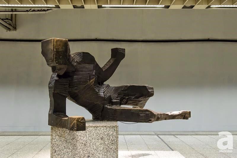 Τίτλος: Θνήσκων Πολεμιστής Θέση: Σταθμός Εθνική Άμυνα (Αποβάθρα του σταθμού) Έτος Κατασκευής: 1971 Υλικό Κατασκευής: Χαλκός Καλλιτέχνης: Δημήτρης Καλαμάρας